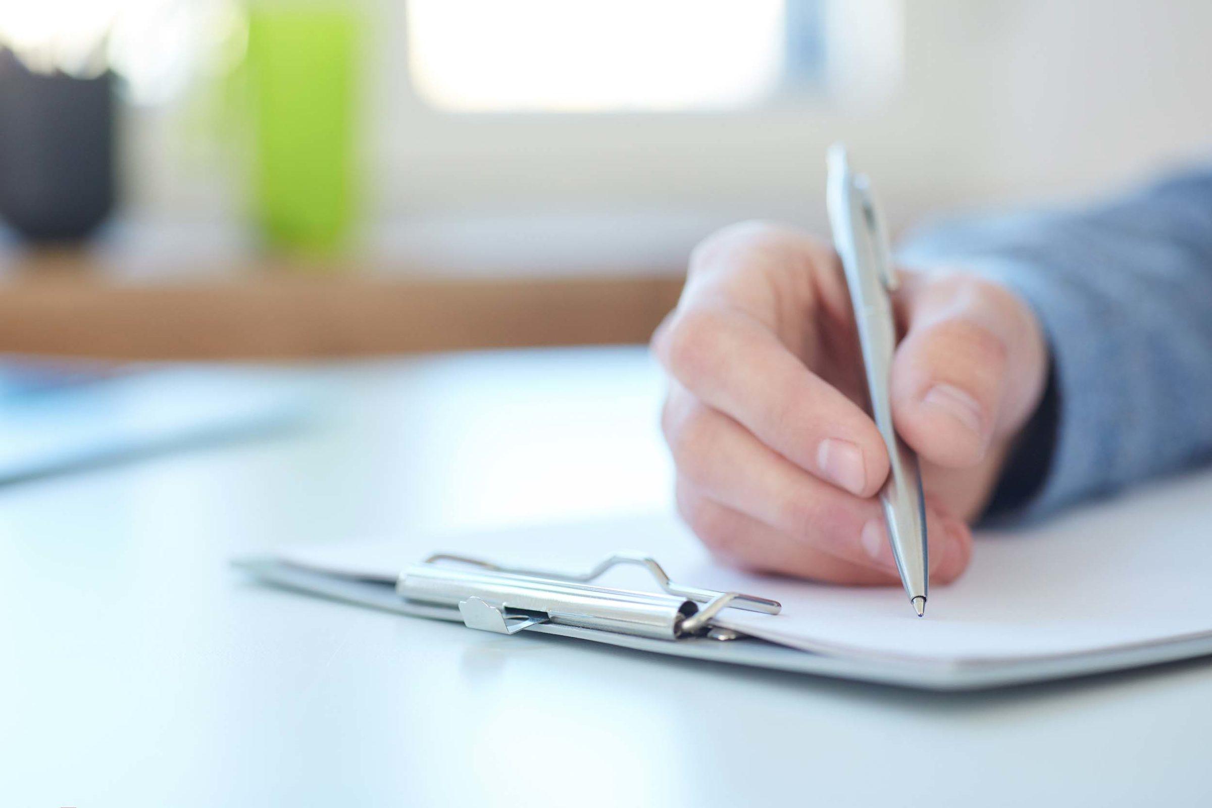 Schufa Auskunft: Hand haelt Stift über Dokument