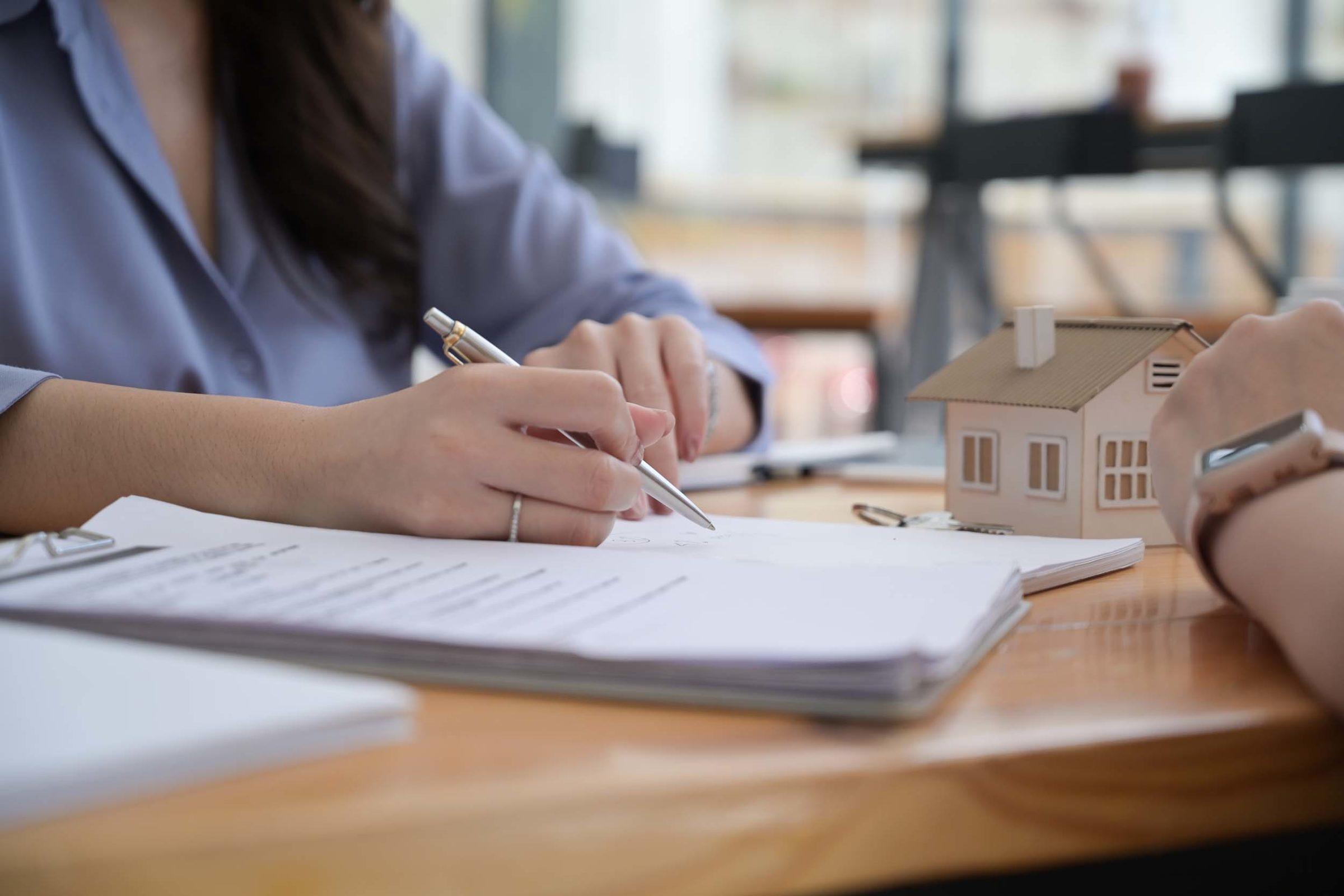 Hausordnung: Frau zeigt mit Stift auf ein Dokument