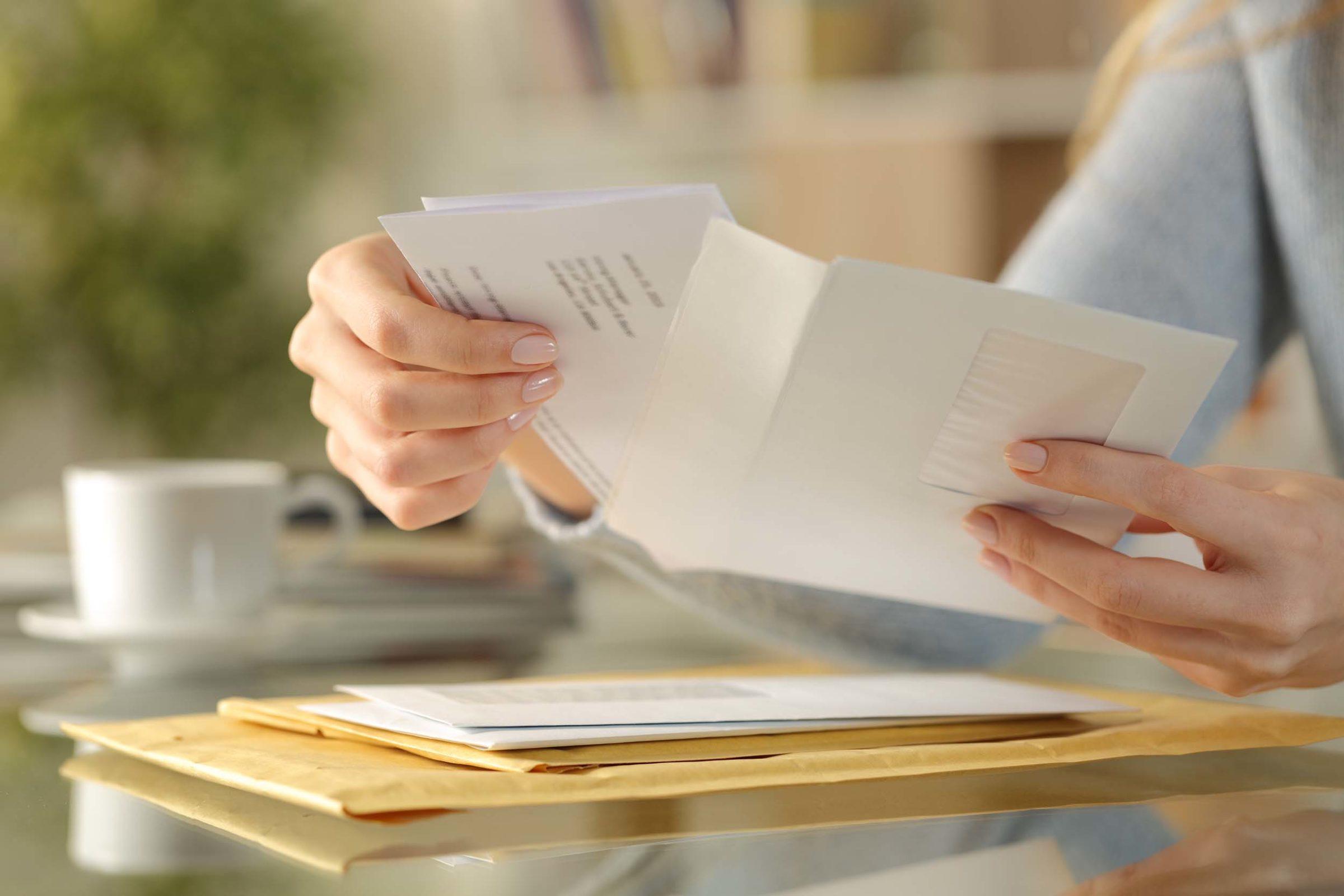 Kuendigungsbestaetigung: Frau legt Brief in einen Umschlag